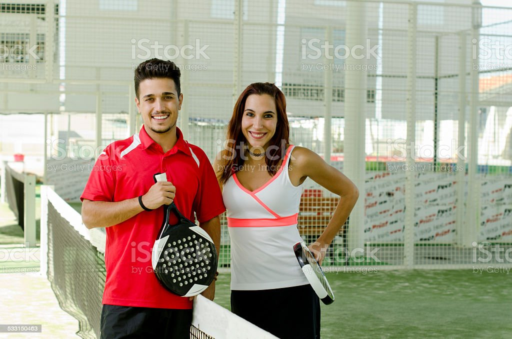 Paddle tennis couple posing in court stock photo