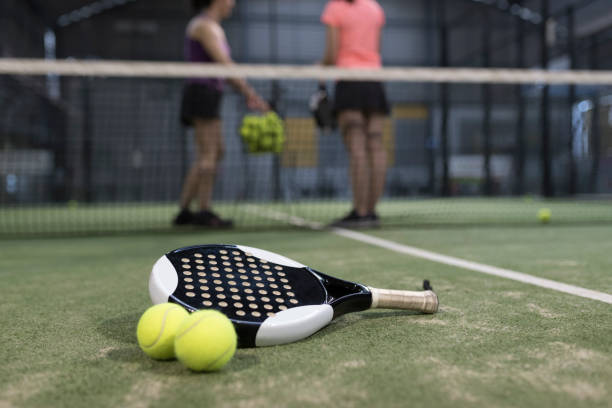 paddle tennis objects on turf ready for tournament and women in background - racket stock pictures, royalty-free photos & images