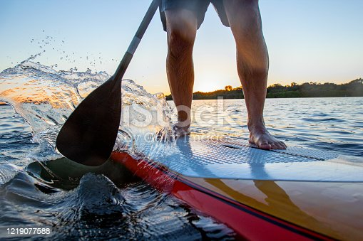 Detail of a man on stand up paddle board. Stand up paddler at sunset, paddle board sport. A tourist practicing a water sport during his vacations.