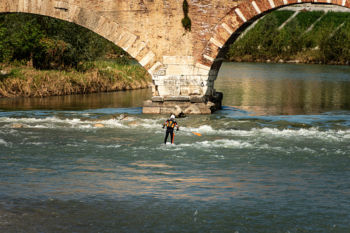 Verona, Italy - Sept 19th, 2020: Verona, a man on his Stand up Paddleboarding (SUP) paddling in the rapids of the River Adige, Ponte Pietra (Stone Bridge), Veneto, Italy, Europe.