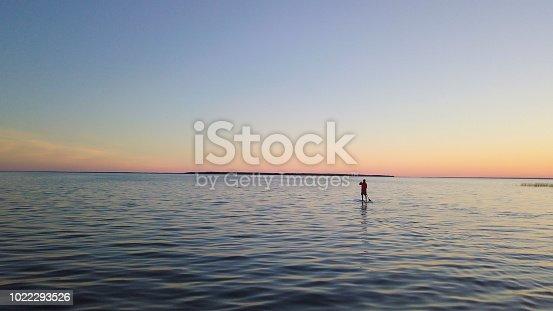 Paddleboarding on lake during sunrise or sunset.