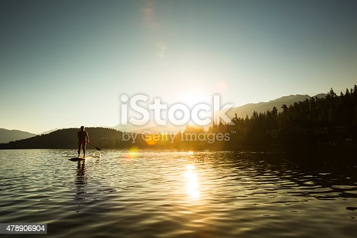 Silhouette of young Asian female paddle boarding in calm waters. Horizontal photograph with lens flare.