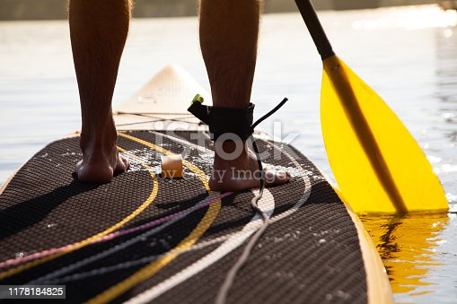 Man stand up on standup paddle board with yellow paddle, close-up view
