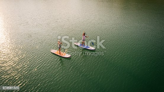 Aerial view of couple paddleboarding on the lake.