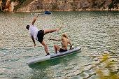 Tattooed couple having fun on paddleboard on the lake. Burst shot 6 of 10.