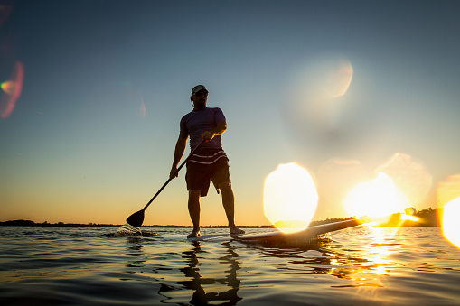 Silhouette of a man on stand up paddle board with water drops in the lens. Stand up paddler at sunset, paddle board sport. A tourist practicing a water sport during his vacations.