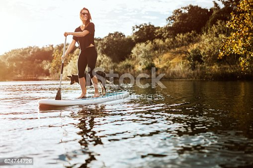 istock Paddleboarding Woman With Dog 624744726