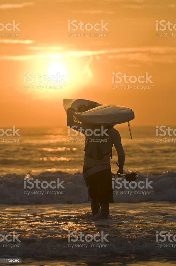 Paddler with surfski on shoulder at sunrise royalty-free stock photo