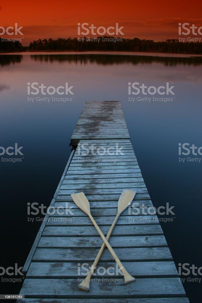 Paddles on Lake Dock at Dusk stock photo
