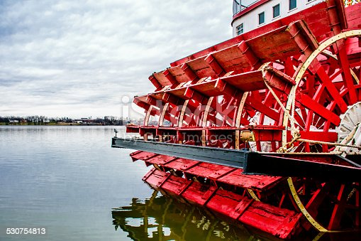 Red and white paddlewheeler docked on the rivers edge.