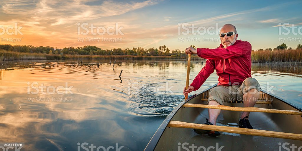 paddling canoe at sunset stock photo