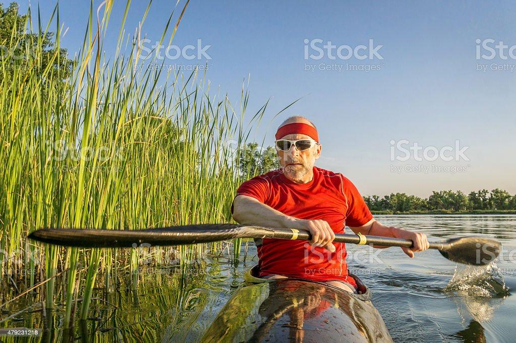 paddling racing sea kayak on lake stock photo