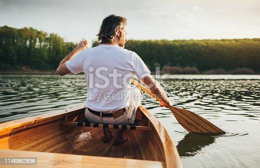 Rear view of male canoeist paddling the wooden canoe with oar.