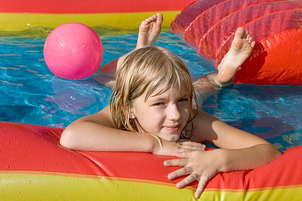 Paddling-pool A small blonde girl dabbles lying prone in a paddling-pool. sole of foot stock pictures, royalty-free photos & images