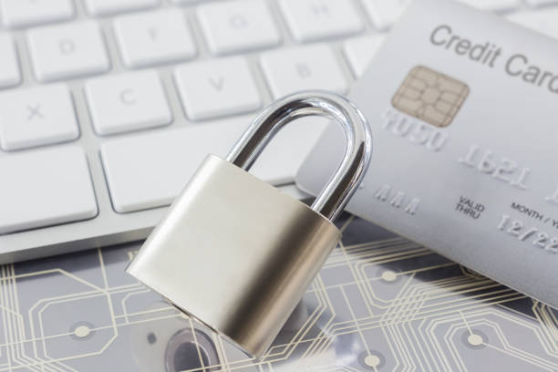 Padlock and credit card on keyboard and electronic circuits. stock photo