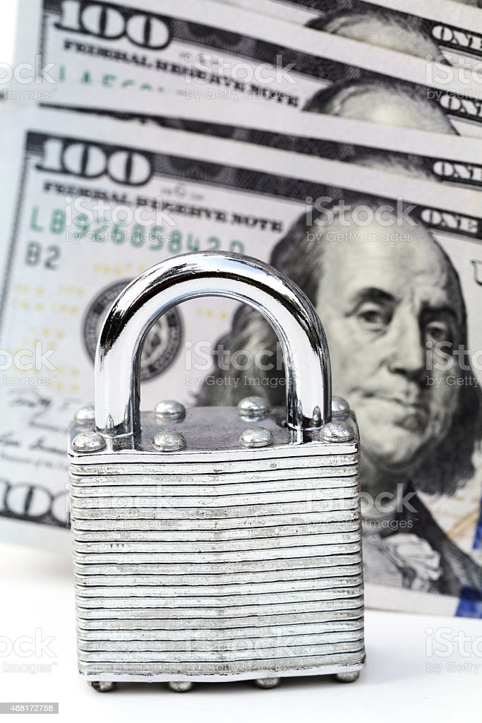 Padlock in front of group of 100 dollar bills stock photo