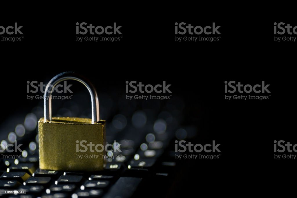 Padlock on a keyboard against dark background. Internet data privacy...