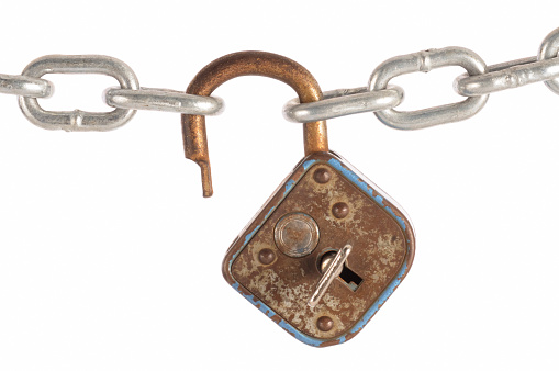 Old Russian made padlock is on a chain.  Isolated on white,