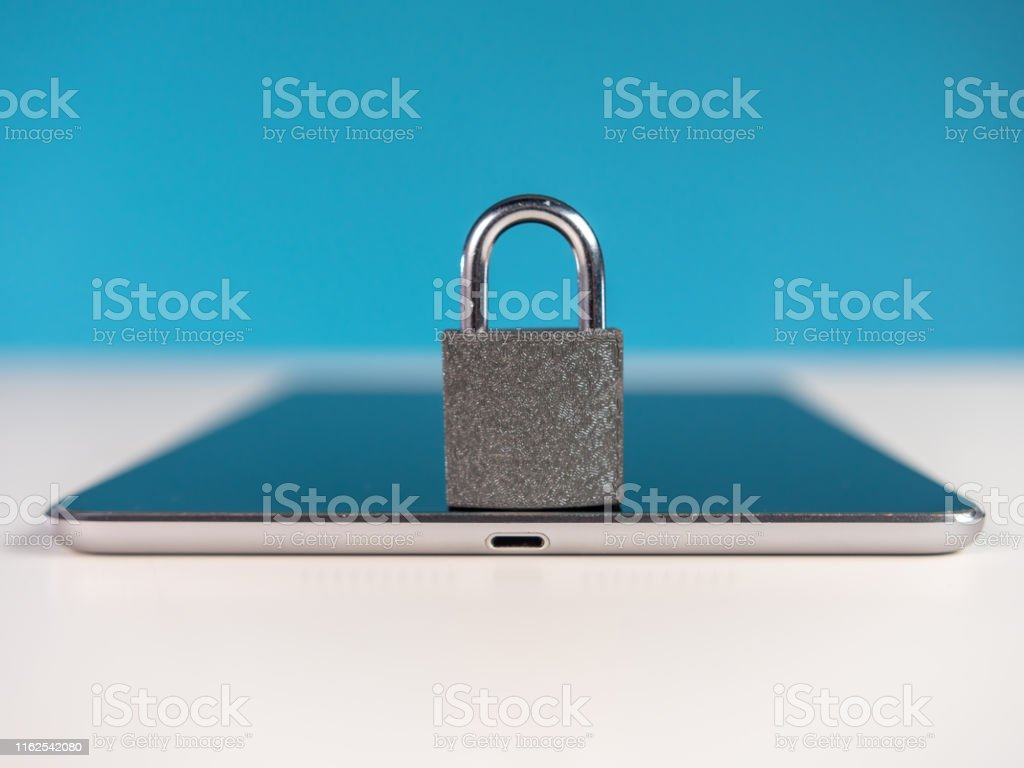 Padlock on portable information device screen. The scene is situated...