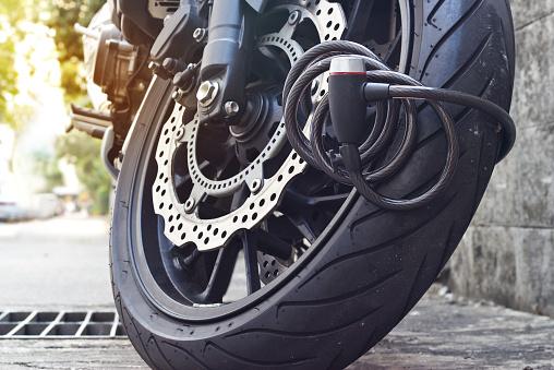 padlock security lock blocking the motorcycle wheel on street