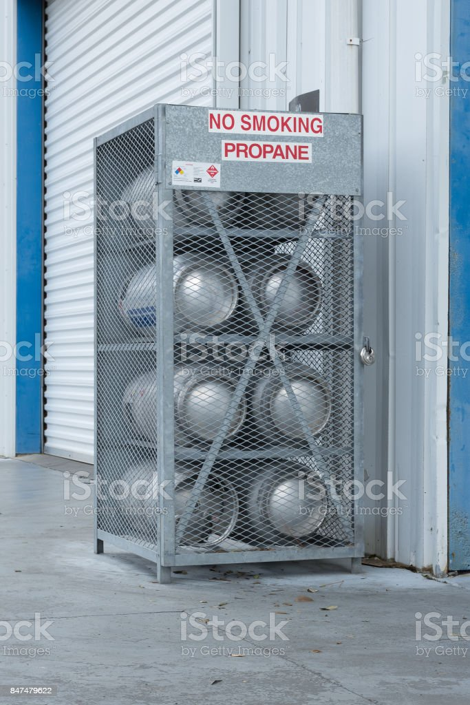 Padlocked steel cage containing eight propane gas tanks outside building stock photo