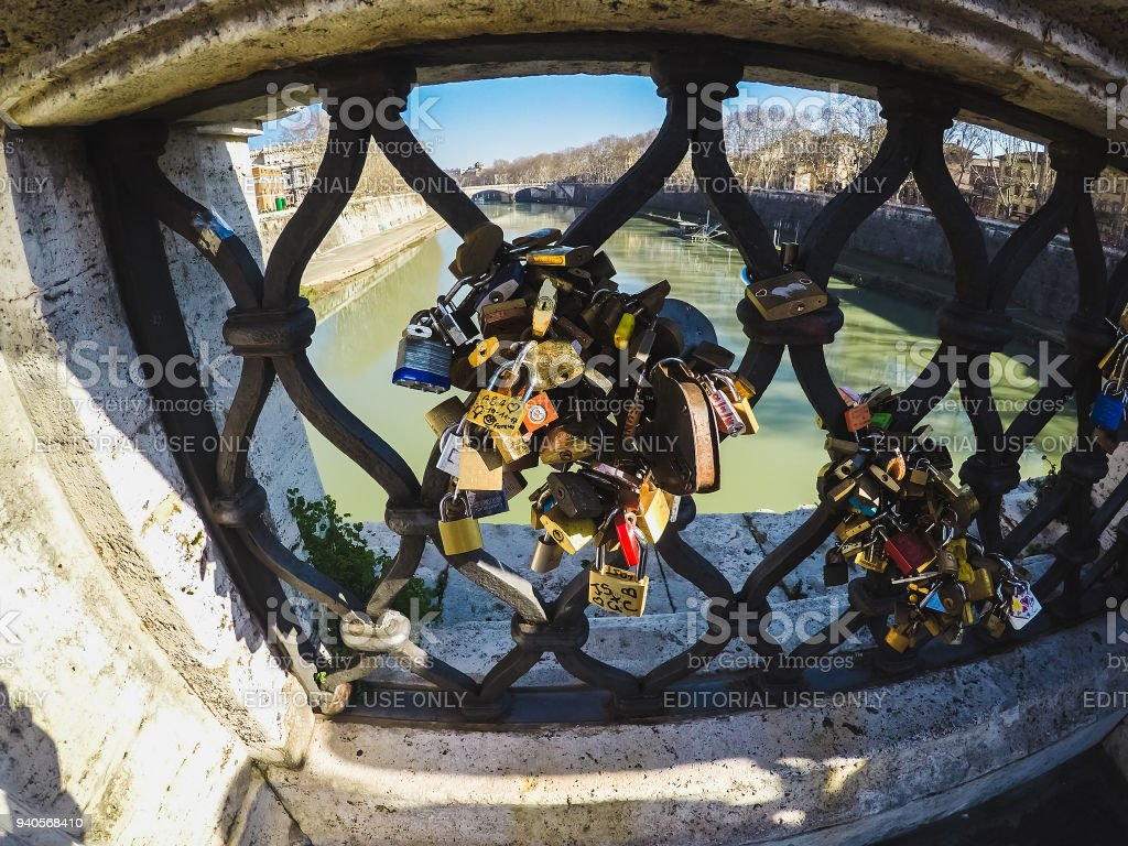 Padlocks locked with names written on it at Ponte Sant'Angelo stock photo