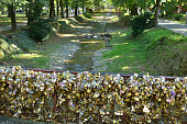 Bridge of Love with lots of padlocks and rivulet with trees on riversides in Vrnjacka Spa