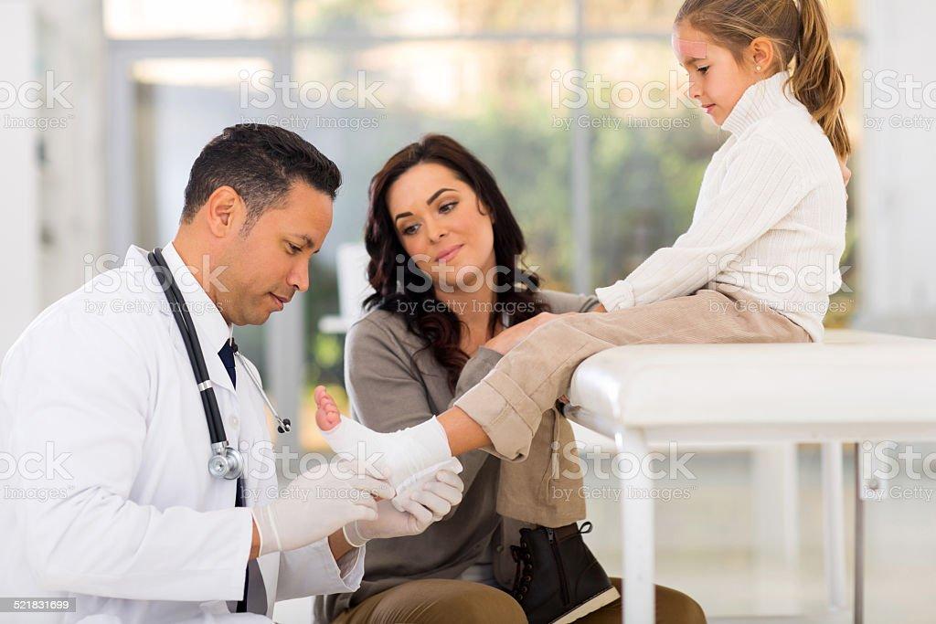 paediatrician bandage little patient's ankle stock photo