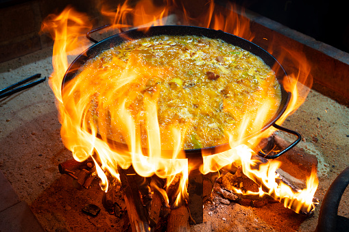 Paella Of Valencia Real Recipe Preparing On Fire Firewood Stock Photo - Download Image Now