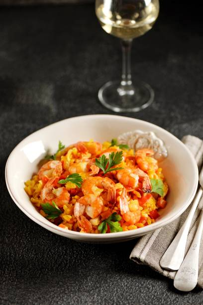 Paella or risotto with shrimp tails, carrots, onions, bell peppers, white wine and chicken stock. stock photo