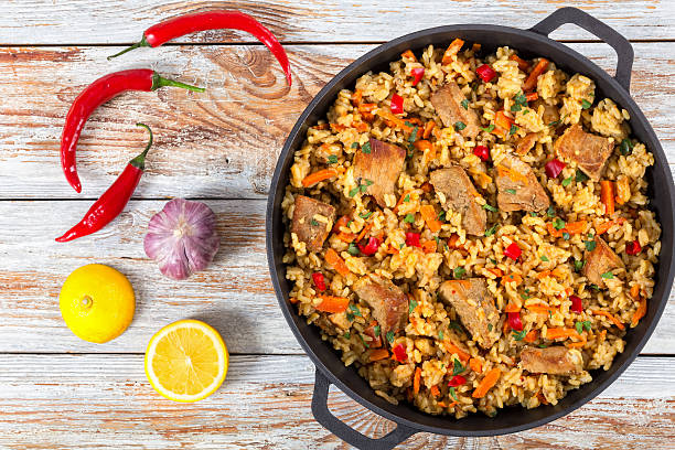 paella with meat, pepper, vegetables and spices - paella stock photos and pictures