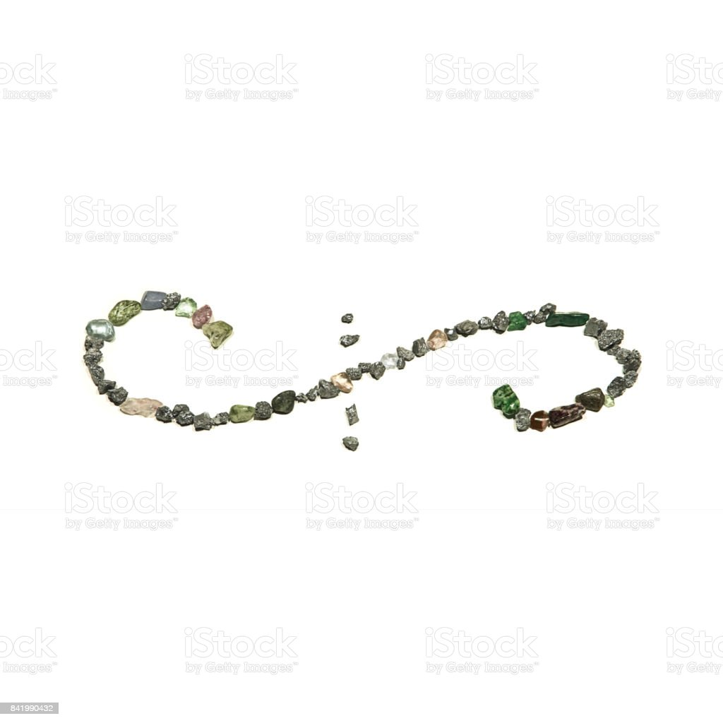 A page divider swirl symbol made from black and green shiny rocks and gems. The picture is reflective of color, texture, symbols, separated, white stock photo