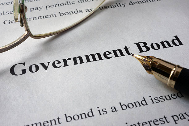 page of newspaper with words government bonds. - stock certificate stock photos and pictures