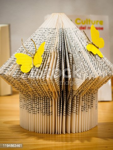 Pages of a book folded to shape it with decorative butterflies. Reading concept. (translation: culture)