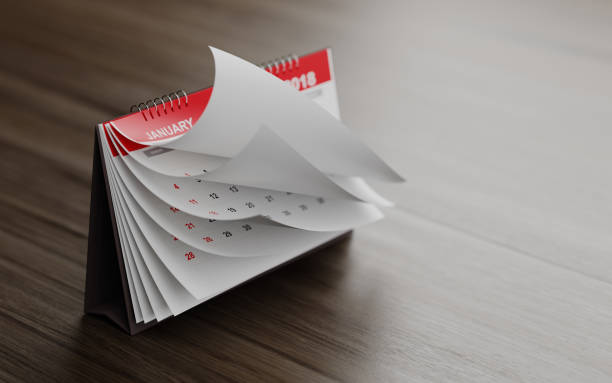 pages of a red calendar standing on wood surface are folding - calendar stock photos and pictures