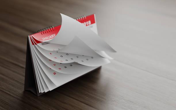 Páginas de un calendario rojo sobre superficie de madera están plegable - foto de stock