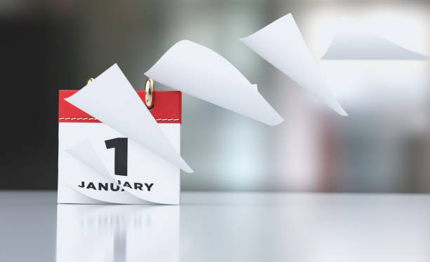 Pages Of A Red Calendar Standing Over Defocused Background Are Flying Away stock photo