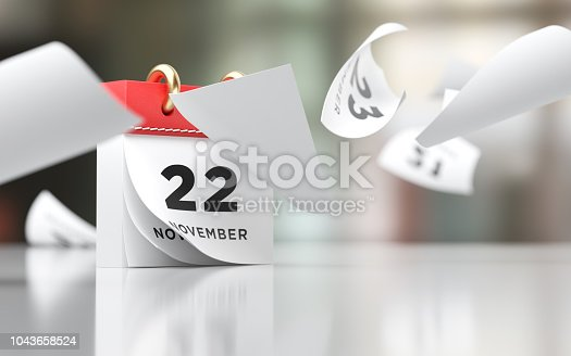 Pages of a red calendar standing over defocused background are flying away. November 22 writes on the calendar. Horizontal composition with copy space. Thanksgiving concept with selective focus.