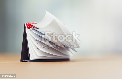 Pages of a red calendar standing over defocused background surface are folding. Horizontal composition with copy space. Calendar and reminder concept with selective focus.