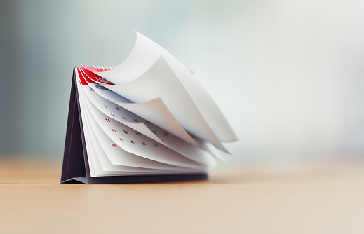 Pages Of A Red Calendar Standing Over Defocused Background Are Folding