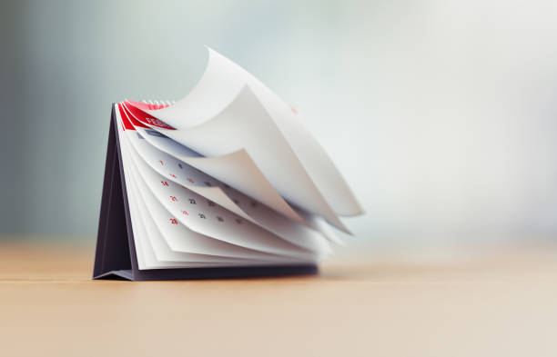 Pages Of A Red Calendar Standing Over Defocused Background Are Folding stock photo