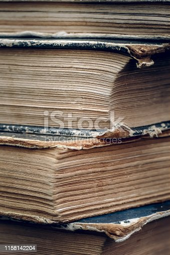 Frayed, yellowed, dark pages of old books closeup