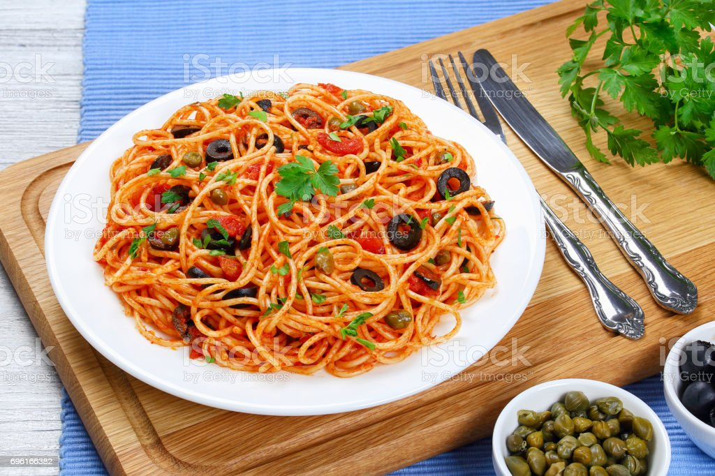 paghetti with tomato sauce, capers and olives stock photo