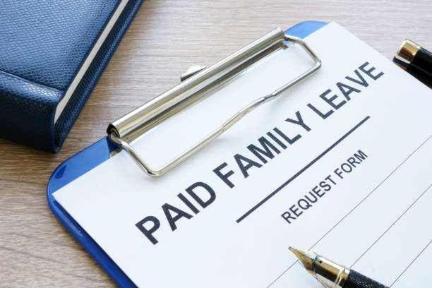 Paid family leave form in clipboard and note pad. - foto stock