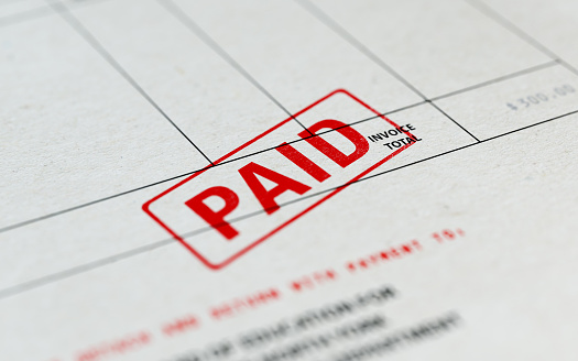 Close-up picture of an invoice with red paid stamp with selective focus. Great use for financial concepts.
