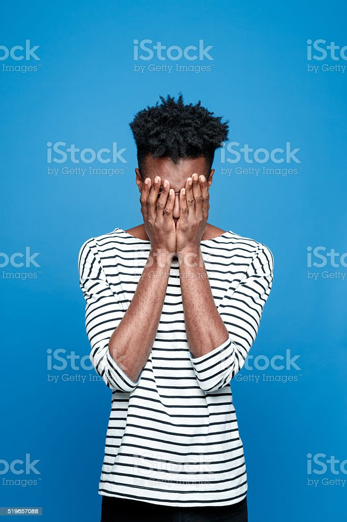 Pain, Afro american guy hiding his face in hand Studio portrait of afro american young man wearing striped top hiding his face in hands. Studio portrait, blue background. Adult Stock Photo