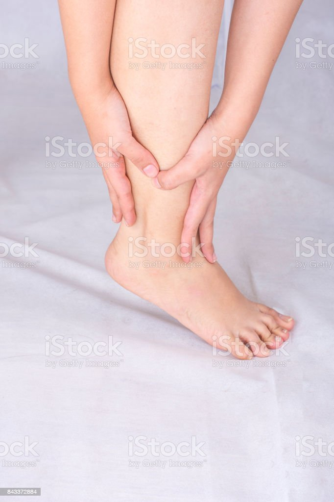 Pain concept with a woman hands catching ankle stock photo