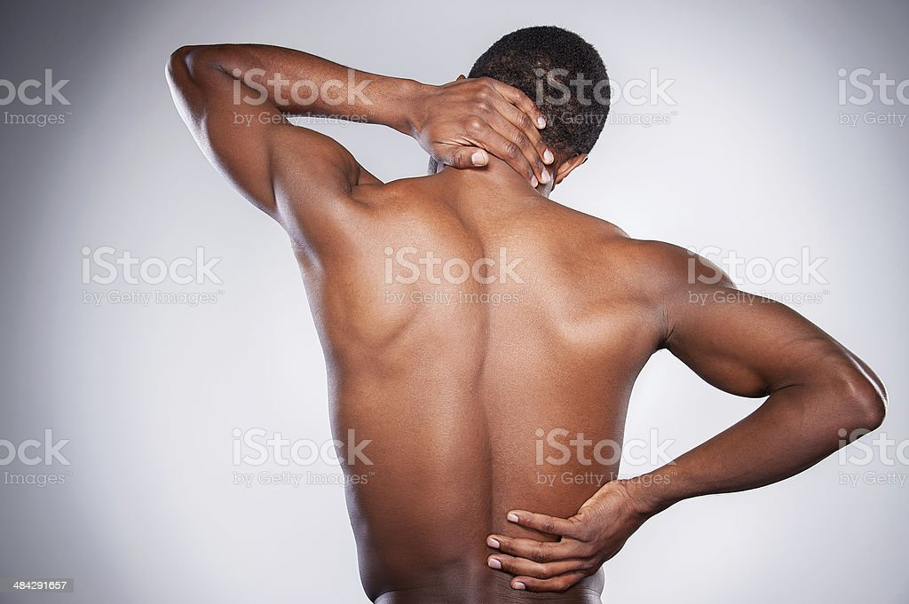Pain in joint. Rear view of young shirtless African man touching his neck and hip while standing against grey background Adult Stock Photo