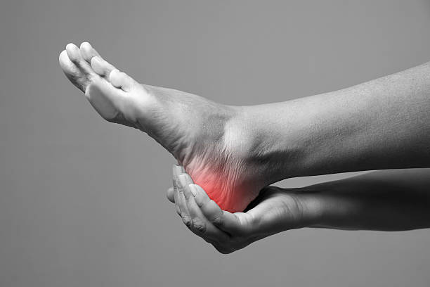 pain in the foot on a gray background - human foot stock photos and pictures