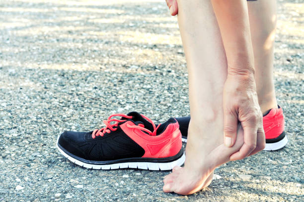 pain in the foot.running injury leg accident- sport woman runner hurting massaging painful sprained ankle in pain.athlete woman has heel injury, sprained ankle during running training. - human foot stock photos and pictures